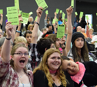 Youth attendees voting at General Assembly, smiling with arms around each other
